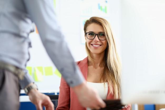 A mulher de óculos está sentada no escritório e sorri