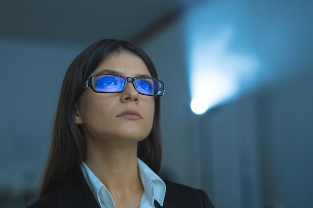 A mulher de óculos no fundo do projetor