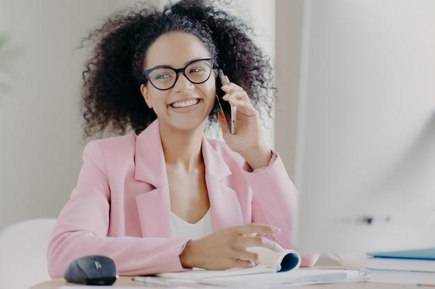 A mulher de pele escura de cabelos muito encaracolados gosta de conversar por telefone com o colega