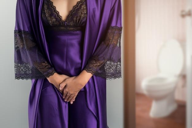 A mulher de pijama roxa de cetim e roupão acorda para ir ao banheiro