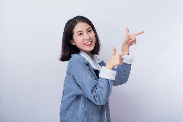 A mulher de sorriso asiática nova aponta sua mão no espaço do fundo para o produto