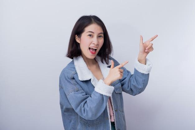 A mulher de sorriso caucasiano aponta sua mão no fundo, menina asiática nova feliz positiva que veste o retrato azul da roupa ocasional