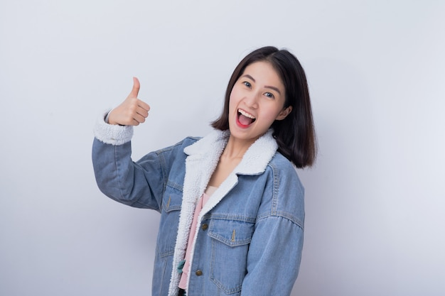 A mulher de sorriso caucasiano que mostra sua mão manuseia acima no bom trabalho do conceito, menina asiática nova feliz positiva que veste o retrato azul da roupa ocasional
