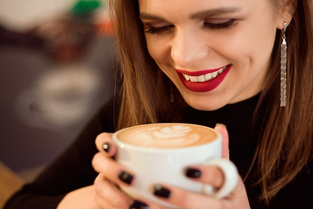 A mulher de sorriso de um bom humor aprecia a xícara de café que senta-se em um café.