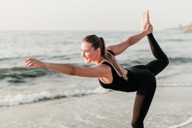 A mulher de sorriso desportiva bonita pratica o asana da ioga que está em uma perna que enfrenta o sol