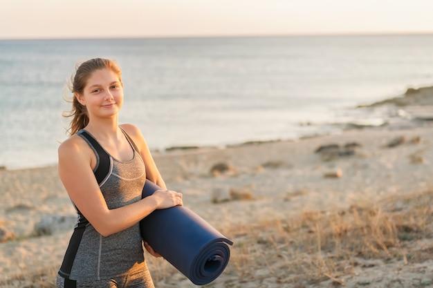 A mulher de sorriso loura nova dos esportes está andando para fazer a manhã que estica a prática. menina segurando o tapete de ioga em uma parede do mar ou oceano no verão