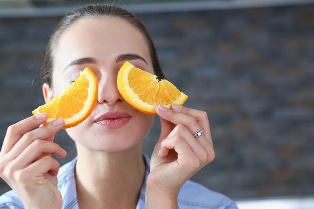 A mulher de sorriso moreno bonita come a laranja cortada