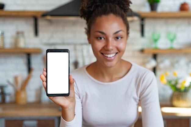 A mulher de sorriso nova do mulato senta-se e mostrando a tela branca do telefone de pilha.