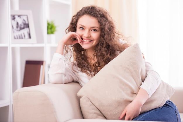 A mulher de sorriso nova está sentando-se em um sofá em casa.