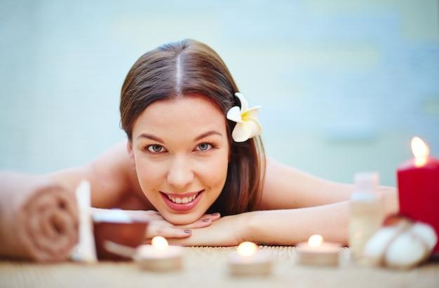 A mulher de sorriso recebendo tratamento spa