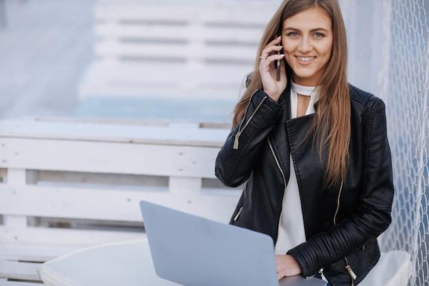 A mulher de sorriso senta-se em um banco branco falando em seu telefone com um laptop nas pernas