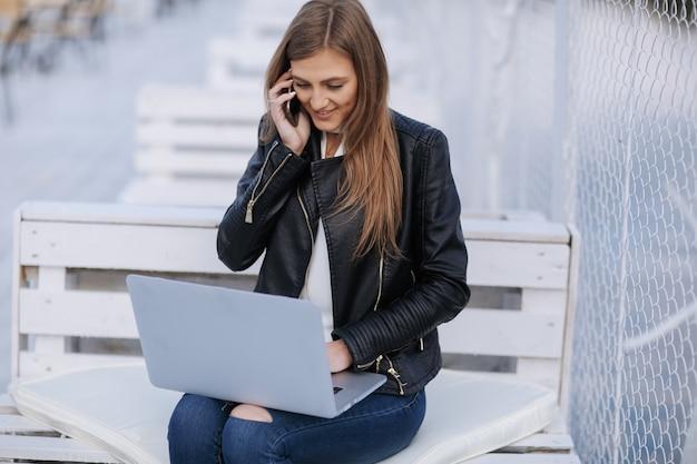 A mulher de sorriso senta-se em um banco branco falando em seu telefone