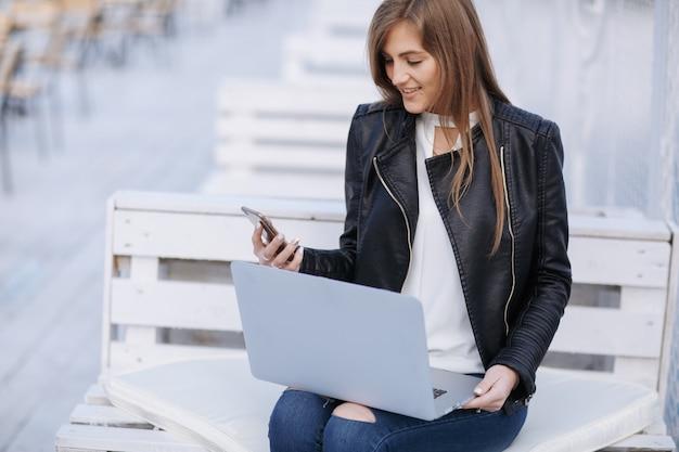A mulher de sorriso senta-se em um banco branco que olha seu telefone