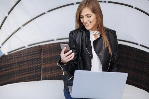A mulher de sorriso senta-se em uma poltrona de vime que olha seu telefone