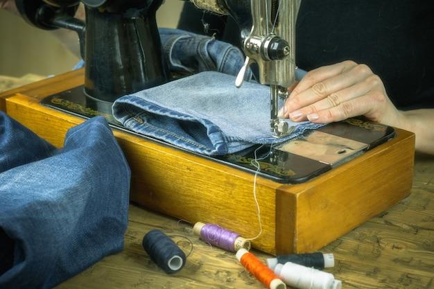 A mulher de suéter preto trabalha na velha máquina de costura.