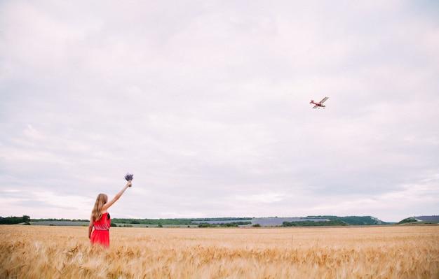 A mulher de vestido vermelho no campo de trigo, acenando para o avião.