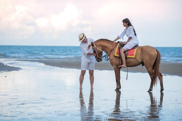 A mulher de viagem asiática que monta um cavalo e ciao com seu amigo de menino na praia do mar.