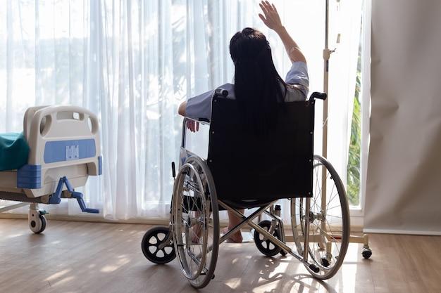 A mulher deficiente em uma cadeira de rodas senta-se da janela na sala paciente.