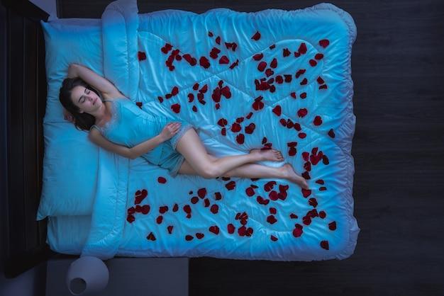A mulher deitada em uma cama com pétalas de rosa. noite, noite, vista de cima