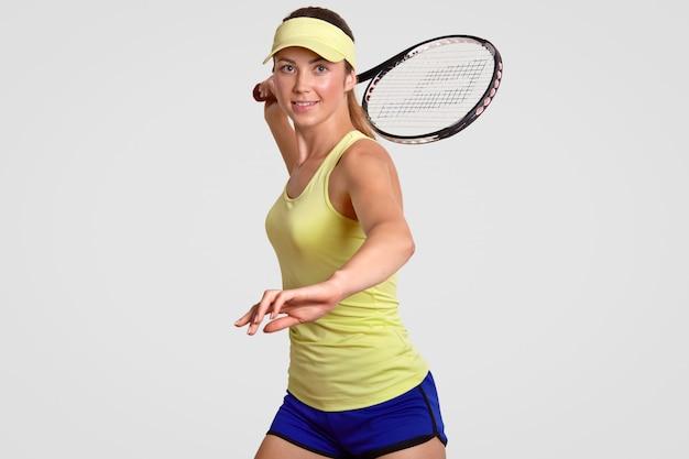A mulher desportiva ativa saudável positiva aquece antes do fósforo, vestido no equipamento ocasional, pronto para bater a bola com raquet, poses contra a parede branca do estúdio. pessoas, motivação, conceito de atividade