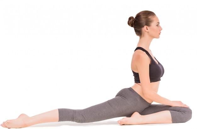 A mulher desportiva nova que faz o esticão exercita no estúdio.