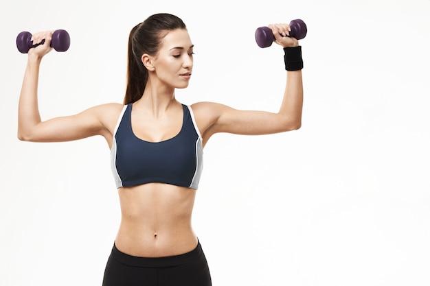 A mulher desportivo no treinamento do sportswear arma-se com pesos no branco.