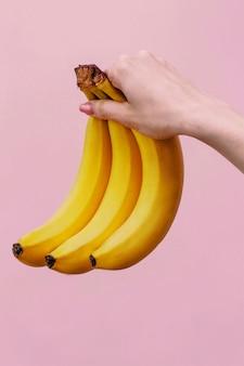 A mulher detém três bananas amarelas na mão