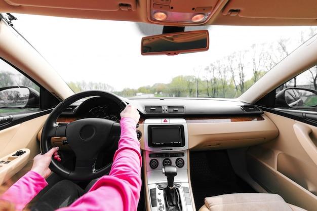 A mulher dirigindo o carro moderno na estrada de asfalto em direção ao pôr do sol