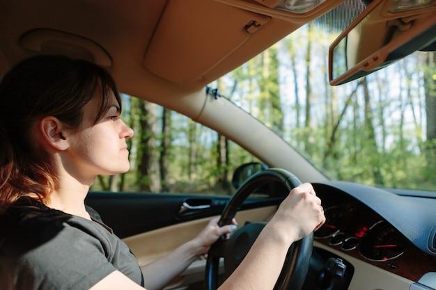 A mulher dirigindo o carro moderno
