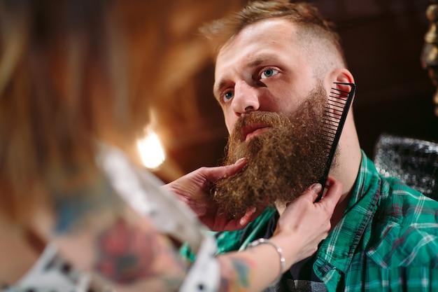 A mulher do barbeiro penteia a barba de um homem