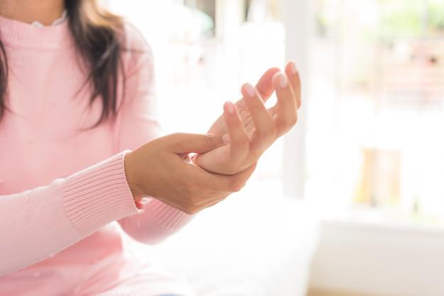 A mulher do close up que senta-se no sofá guarda seu ferimento da mão do pulso, sentindo a dor
