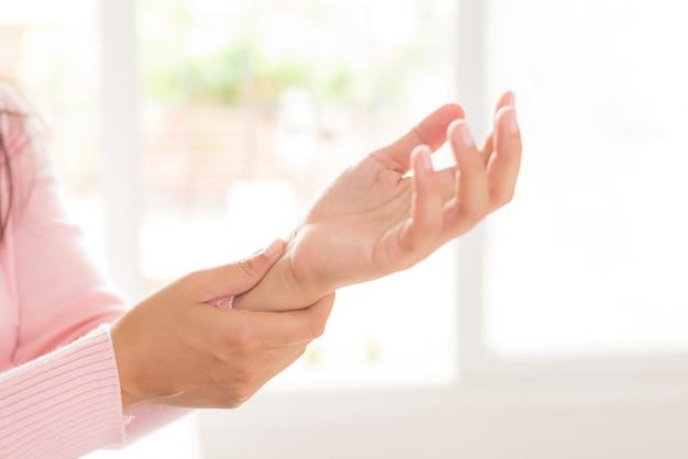 A mulher do close up que senta-se no sofá guarda seu ferimento de mão do pulso, sentindo a dor.
