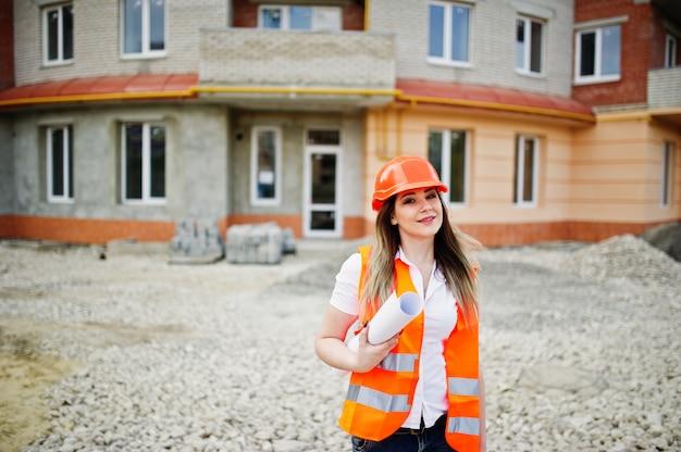 A mulher do construtor do coordenador no colete uniforme e no capacete protetor alaranjado mantem o papel de negócio contra a construção nova