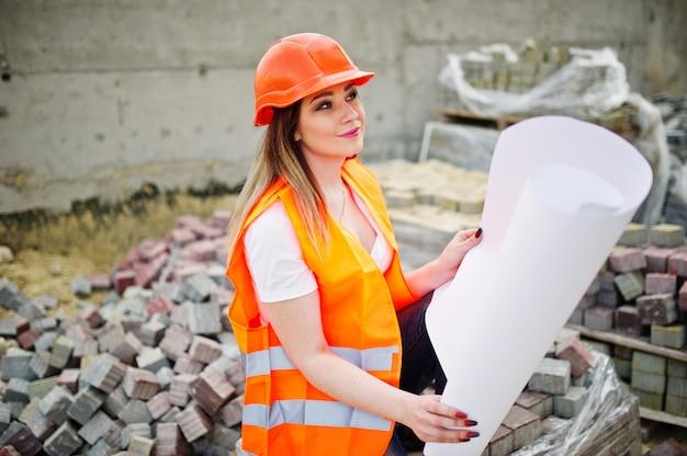 A mulher do construtor do coordenador no colete uniforme e no capacete protetor alaranjado prende o papel do plano do layout do negócio que senta-se na calçada.