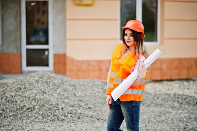 A mulher do construtor do coordenador no colete uniforme e no capacete protetor alaranjado prende o rolo de papel do desenho de negócio contra a construção nova