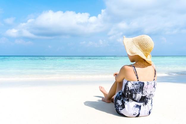A mulher do feriado da praia do verão relaxa na praia no tempo livre.