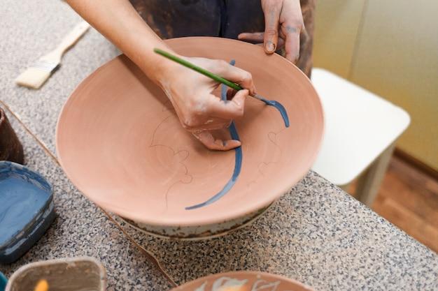 A mulher do oleiro pinta um close da placa cerâmica.