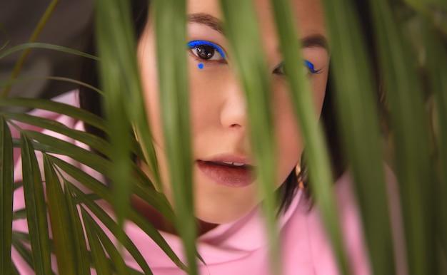 A mulher do retrato com forro colorido dos olhos azuis das setas, olha através das folhas de palmeira.