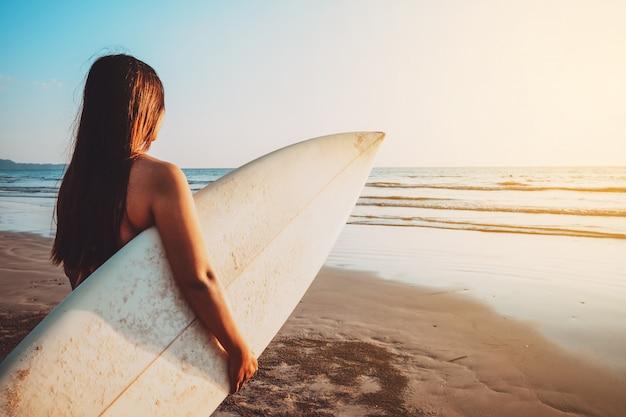 A mulher do surfista no biquini vai surfar. bela mulher sexy com prancha de surf na praia ao pôr do sol. tom da cor do vintage