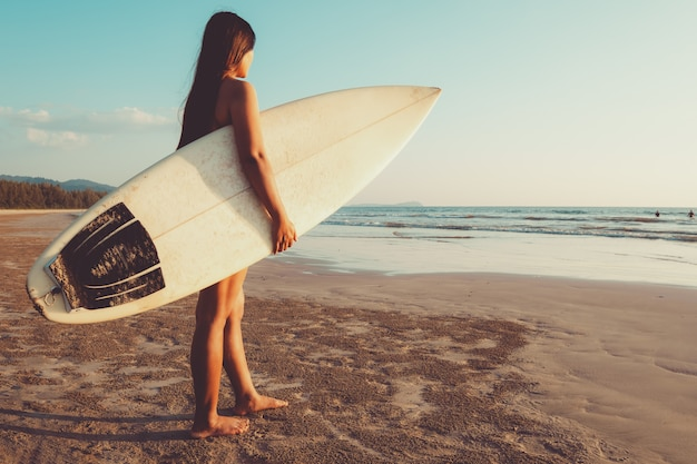 A mulher do surfista no biquini vai surfar. bela mulher sexy com prancha de surf na praia ao pôr do sol.