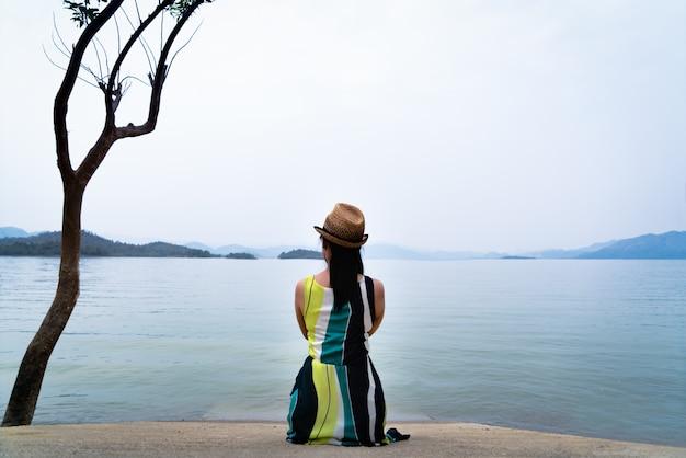 A mulher do viajante aprecia olhando o lago bonito com as montanhas no fundo