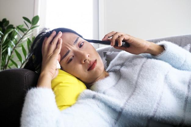 A mulher doente deitada no sofá tinha expressão facial ansiosa, decepção e triste depois de receber más notícias no telefone.