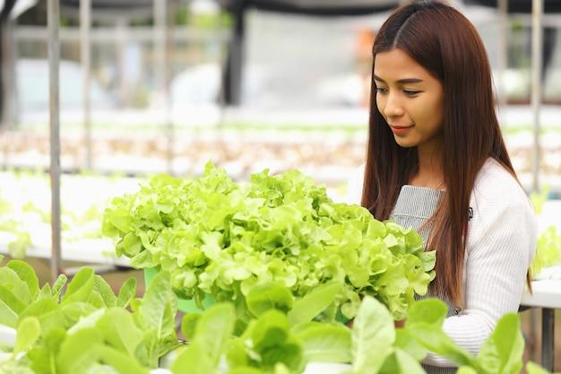 A mulher dona da fazenda hidropônica de vegetais ela e vegetais orgânicos