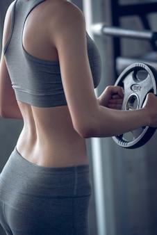 A mulher dos esportes que levanta peso no gym do esporte, bodybuilding e perde o conceito do peso.