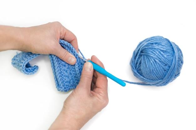A mulher duas mãos tricotando roupas de lã do inverno em fundo branco, isolado
