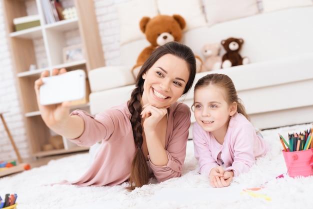 A mulher e a menina de sorriso encontram-se no tapete fazem o selfie.