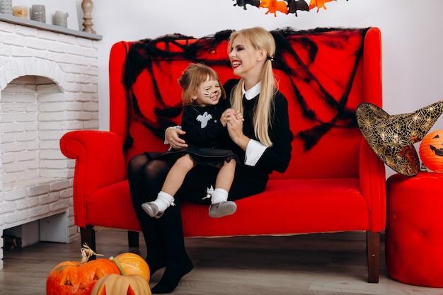 A mulher e a menina têm um tempo engraçado no sofá vermelho. emoção e halloween