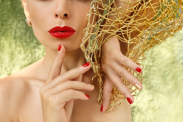 A mulher é loira com unhas e lábios vermelhos curtos