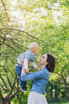 A mulher e o filho descansam no jardim de verão