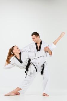 A mulher e o homem de karatê com cintos pretos